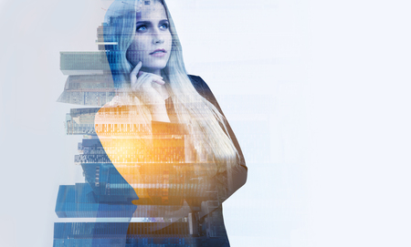 double chin: Blonde businesswoman with hand at chin, office buildings. Double exposure. Concept of work. Stock Photo