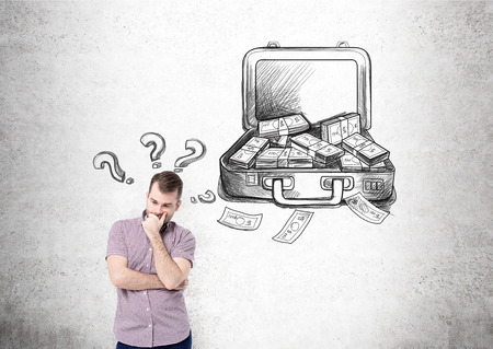 making money: Businessman with hand at chin, open case with money drawn on concrete wall behind, question marks over his head. Concept of making money.