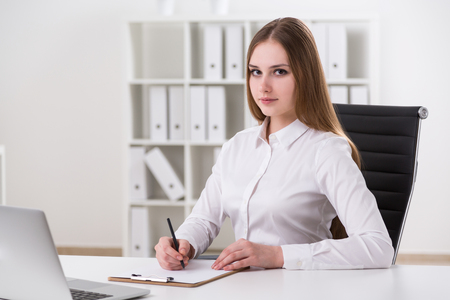 front office: Businessswoman sitting in front of laptop and making notes, looking in front. Office. Concept of work. Stock Photo