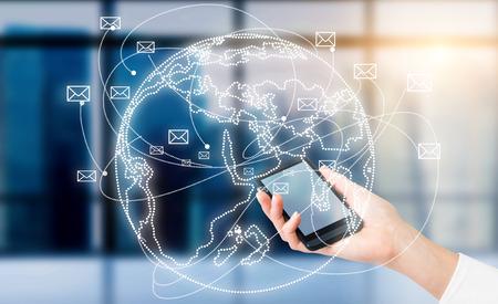mundo manos: Mano con el teléfono inteligente, globo con los sobres que vuelan alrededor del mismo. Ventana en el fondo. Concepto de comunicación.