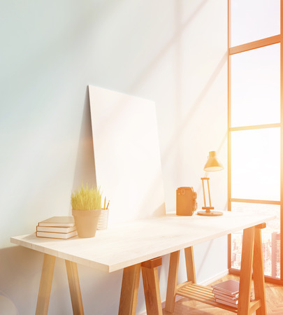 lamp window: Blank frame on white table, books on and under table, lamp, window to the right. 3D rendering Stock Photo