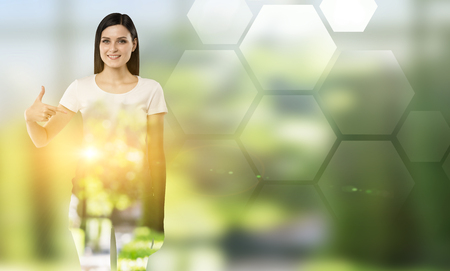 jogging in nature: Young woman pointing at blank hexagonals to the right. Blurred green background. Concept of nature. Stock Photo