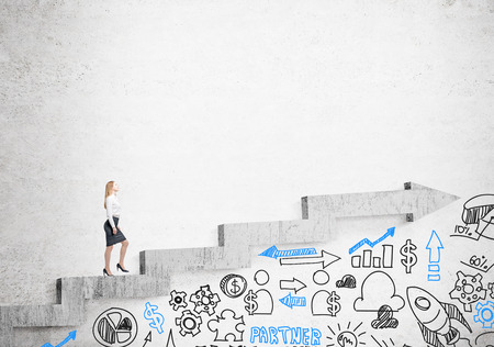 career up: Businesswoman going up stairs shaped by concrete arrow, business icons under it. Concrete background. Concept of career growth.
