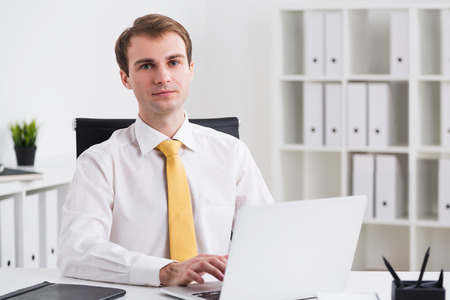 front office: Businessman sitting at computer and looking in front, office at background. Concept of work. Stock Photo