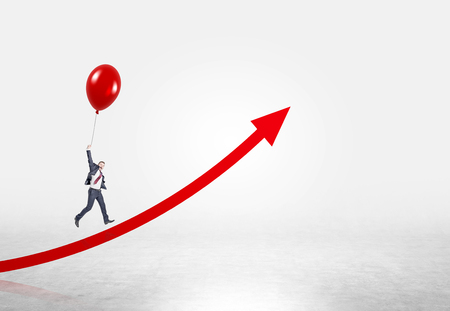 career up: Businessman flying up on red balloon over red arrow. Concrete background. Concept of career growth.