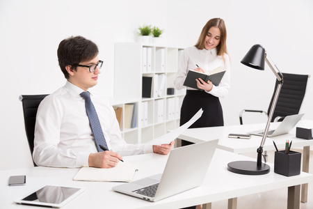 datebook: Young businessman looking at paper, office table. Smiling businesswoman with datebook at background. Concept of office assistant.