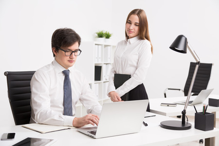 datebook: Young businessman working on computer, office table. Young businesswoman with datebook standing next to him. Concept of office work. Stock Photo