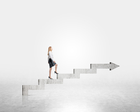 career up: Businesswoman going up stairs shaped by concrete arrow. Concrete background. Concept of career growth.