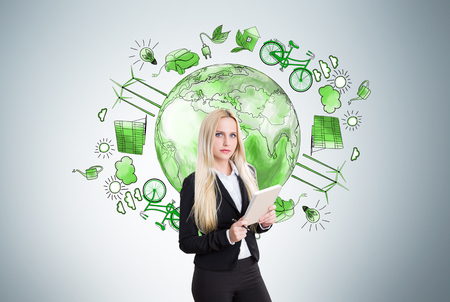 energy sources: Young businesswoman with notebook, green earth and alternative energy sources drawn behind her. Grey background. Concept of  clean environment.