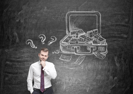 hand on chin: Businessman with hand at chin, open case with money drawn on black wall behind, question marks over his head. Concept of making money. Stock Photo