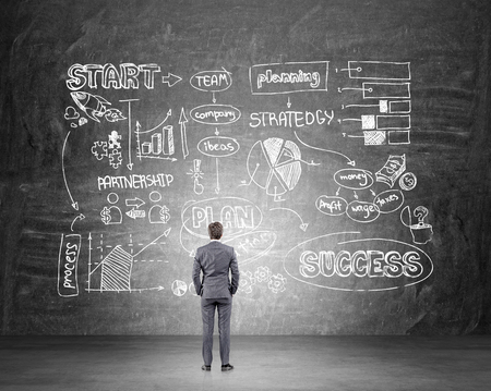 Homme d'affaires avec les mains dans les poches debout devant le mur noir avec système d'entreprise. Vue arrière. Concept de la création d'entreprise.