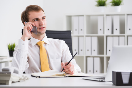 file clerks: Businessman speaking on phone and making notes, looking up, office at background. Concept of communication. Stock Photo