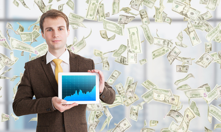 hombre cayendo: El hombre de negocios con la tableta, gráficos de divisas en pantalla, los dólares que caen desde arriba. Ventana en el fondo. El concepto de ganar dinero.