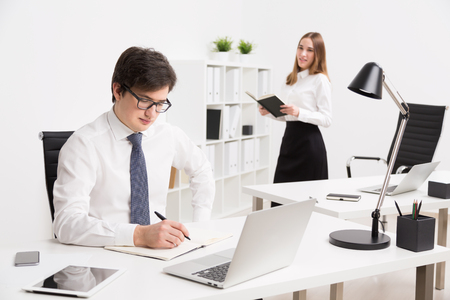 datebook: Young businessman making notes, office table. Smiling businesswoman with datebook at background. Concept of office work.