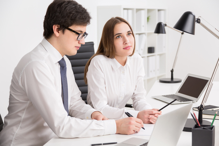 looking aside: Young businessman looking at laptop screen and making notes, businesswoman next to him looking aside. Concept of explanation. Stock Photo