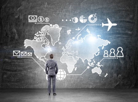 sums: Businessman standing in front of map drawn on blackboard, money, people and communication pointsvand plane  on it. Concept of business logistics. Stock Photo
