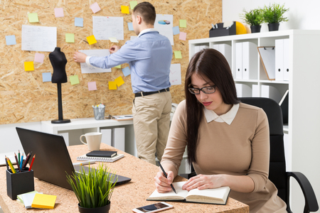 pinning: Woman making notes, man pinning paper to wall. Office. Concept of work.