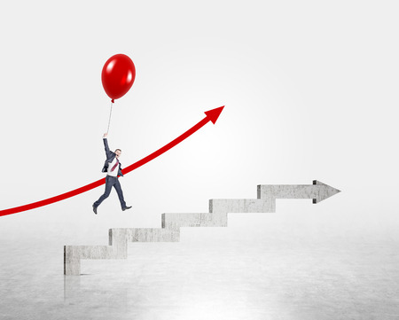 concrete stairs: Businessman flying up on red balloon over stairs shaped by concrete arrow. Concrete background. Concept of career growth.
