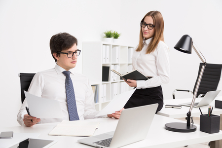 datebook: Serious young businessman looking at documents, office table. Smiling assistant with datebook sitting on his table. Concept of office assistant.