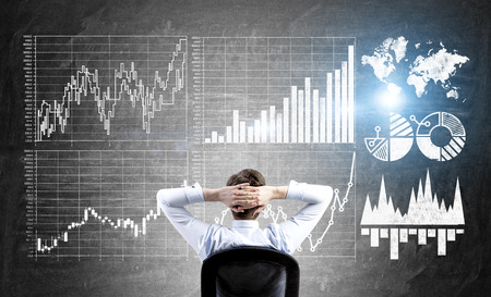 deal making: Research concept with businessman sitting in front of wall with forex charts