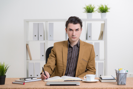 file clerks: Businessman in smart suit at table, book open in front of him, making notes. Office at background. Concept of work.