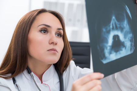 hard: Female doctor looking at X-rays, close up. Office at background. Concept of work.