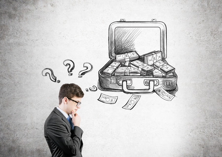 making money: Businessman with hand at chin, open case with money drawn on concrete wall behind, question marks over his head. Side view. Concept of making money.
