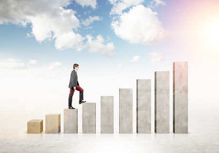concrete stairs: Businessman going up stairs shaped by concrete blocks. Sky at background. Concept of career growth. Stock Photo