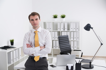 front office: Businessman standing with hands crossed and looking in front, office at background. Concept of work.