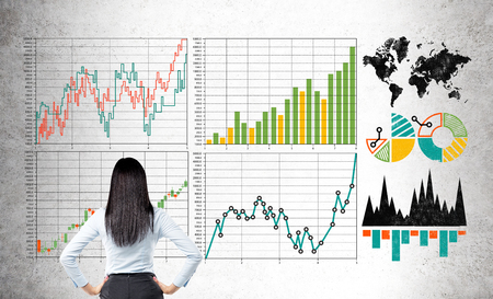 forex: Research concept with businesswoman looking at forex graphs on light concrete wall