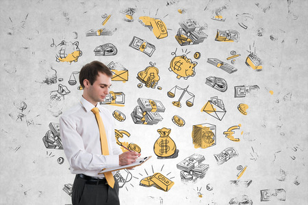 Businessman writing in notepad, standing at concrete wall with money sketches