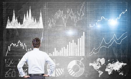 Koncepcja Badania z biznesmenem patrząc na forex wykresy na ciemnoszarą betonową ścianę