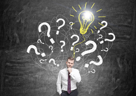 cement solution: Idea concept with businessman standing against wall with question mark and bulb sketch Stock Photo
