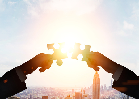puzzle people: Teamwork concept with businessmen putting puzzle pieces together on cityscape background with sunlight Stock Photo
