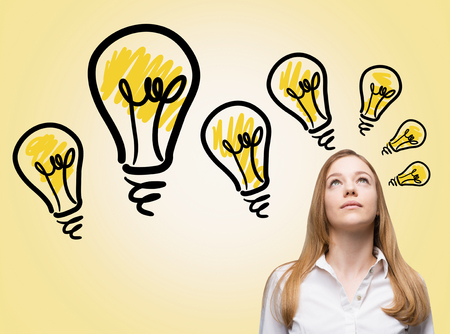 over white: Businesswoman looking up, several yellow bulbs over her head. White background. Concept of new ideas. Stock Photo