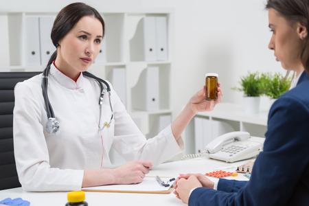 Docteur écoute patient et tenant une bouteille de pilules. Pills sur la table. Concept de consultation médicale. Banque d'images