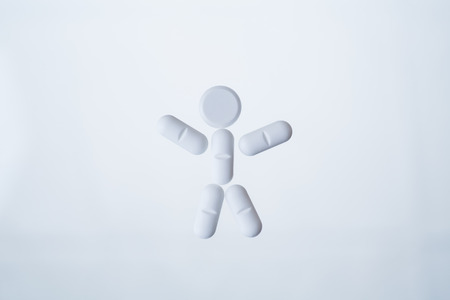 white pills: Human character made out of white pills isolated on light background