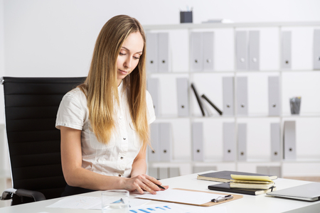 swivel chairs: Female sitting at desk with items in office