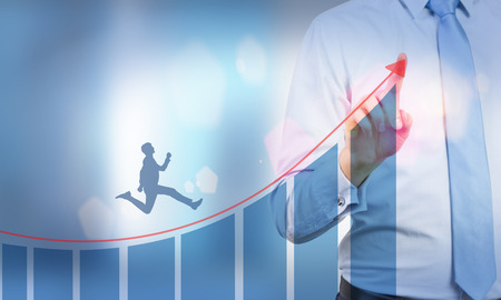 upward graph: Businessman drawing arrow above abstract bar graph with man silhouette running upward. Double exposure