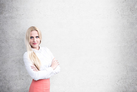 busineswoman: Pretty busineswoman in shirt and pink skirt with blank concrete wall in the background. Mock up Stock Photo