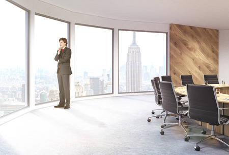 sideview: Businessman in boarding room sideview with panoramic windows revealing New York city view. 3D Rendering Stock Photo