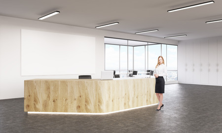 noone: Businesswoman at empty reception with laptops, big white board on wall behind. Concept of reception. Stock Photo