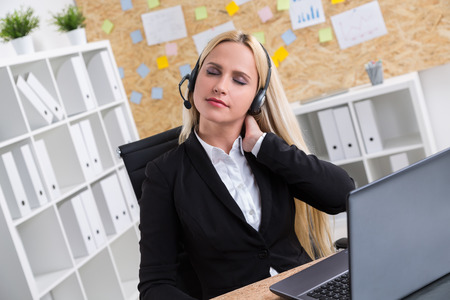 tiredness: Businesswoman in black jacket and headphones with microphone working on computer, touching her neck. Office at background. Concept of tiredness. Stock Photo