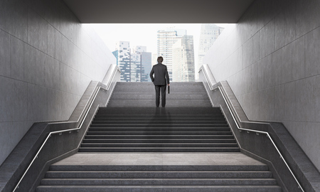 leading the way: Businessman with briefcase climbing stairs in pedestrian subway, going to the city. Concept of success. New York. 3D Rendering