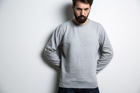Serious man in long sleeved sweatshirt on light grey background Stock Photo