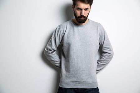sudadera: Serious man in long sleeved sweatshirt on light grey background Foto de archivo