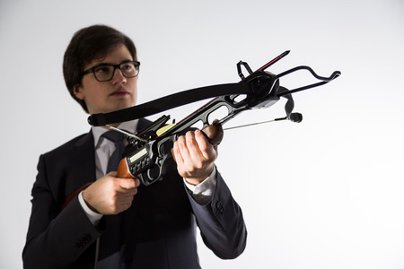 arbalest: Businessman with crossbow in hands looking into the distance on light background Stock Photo