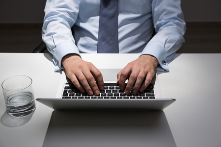 office lighting: Businessman sitting at office desk with glass of water and typing on laptop keyboard. Spot lighting