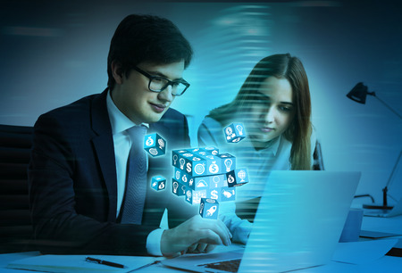 chaos order: Businessman and woman using laptop with digital cubes coming out of the screen