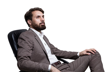 sideview: Sideview of bearded businessman sitting on chair. Isolated on white background. Mock up Stock Photo